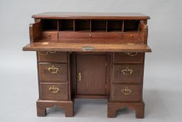 A hardwood kneehole desk in the 19th Century style having pull out desk to frieze, brass drop
