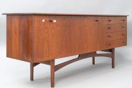 A vintage teak sideboard, in the Long John style , having wide drop flap cocktail or similar section