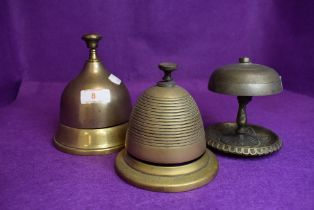 Three desk top brass bell ringers in various forms including bee hive, bell form and art nouveau
