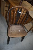 A traditional oak kitchen chair having slat back and turned frame