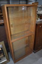 A vintage golden oak glazed bookcase, single piece double height