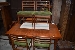 A vintage G plan or similar teak extending dining table with integral butterfly style centre leaf,