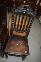 A 19th Century carved oak hall chair having solid seat, vine decoration to back rail, and part twist