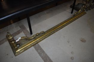 A 19th Century brass ornate fire fender and a pair of complimentary fire dogs