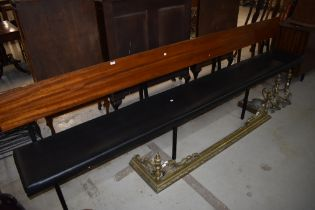 A vintage pew having wood frame and book rail to rear, with vinyl seat, length approx. 300cm