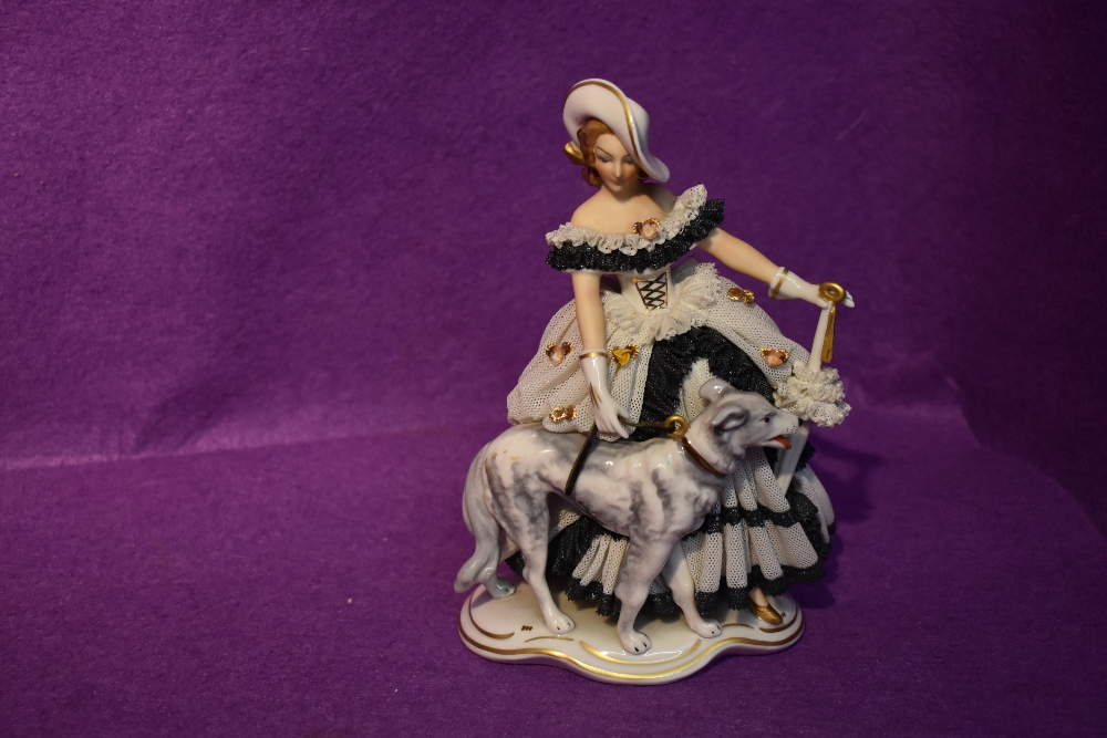 A German reproduction decorative figurine, Crinoline Lady with Dog and Parosol
