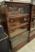 An early 20th Century oak stacking bookcase unit with drawer base and four glazed tiers, in the