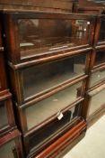 An early 20th Century oak stacking bookcase unit with mismatched mahogany base, having four glazed