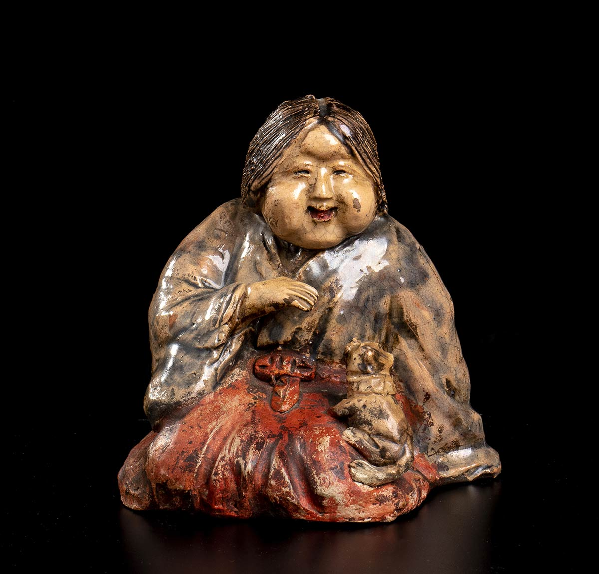 A GLAZED AND PAINTED CERAMIC SCULPTURE OF OKAME WITH A DOGJapan, Meiji period