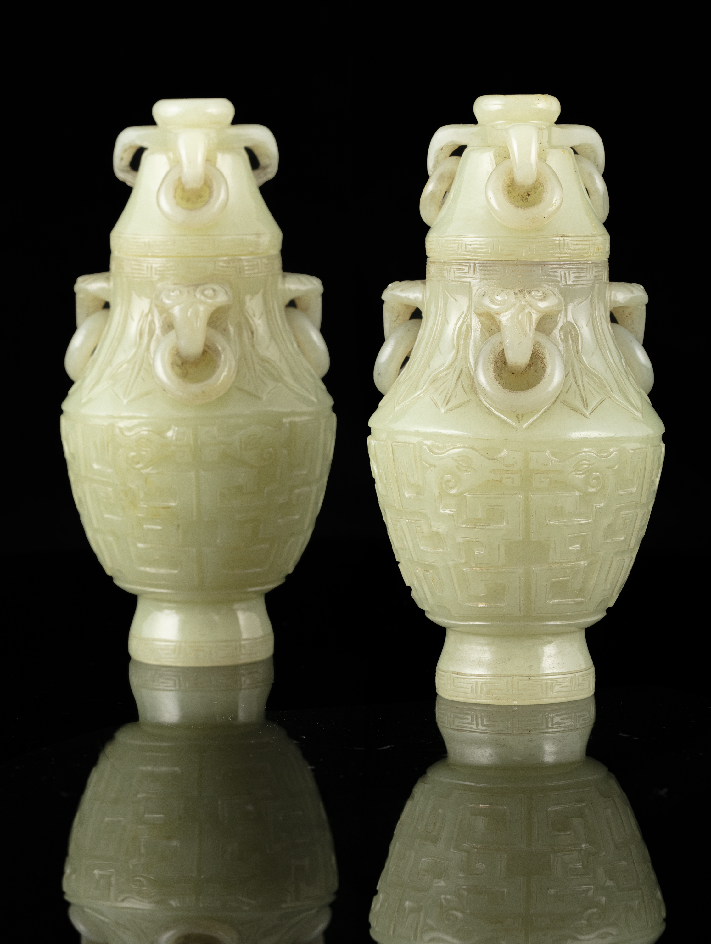 A PAIR OF SMALL JADE LIDDED URNS WITH LOOSE RINGS China, Qing Dynasty, 19th century The body
