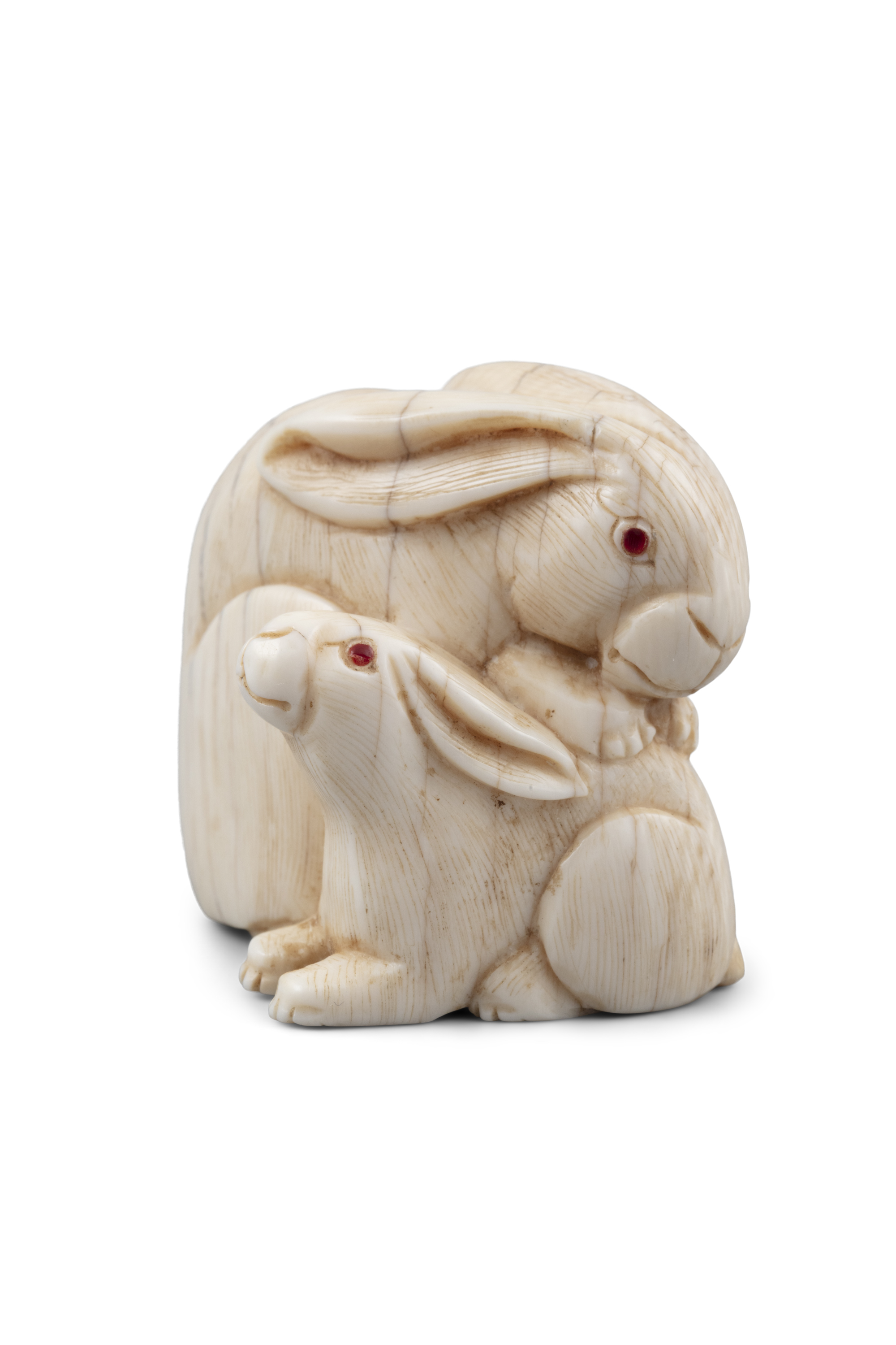 *A SIGNED IVORY 'TWO COILED RABBITS' KATABORI NETSUKE Japan, 19th century With inlaid eyes.