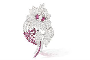 A DIAMOND AND RUBY BROOCH, CIRCA 1950 Designed as a stylised flower, the petals set with