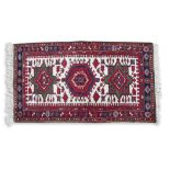 A KAZAK STYLE WOOL RUG, of rectangular shape, with cream ground centre field, woven with three