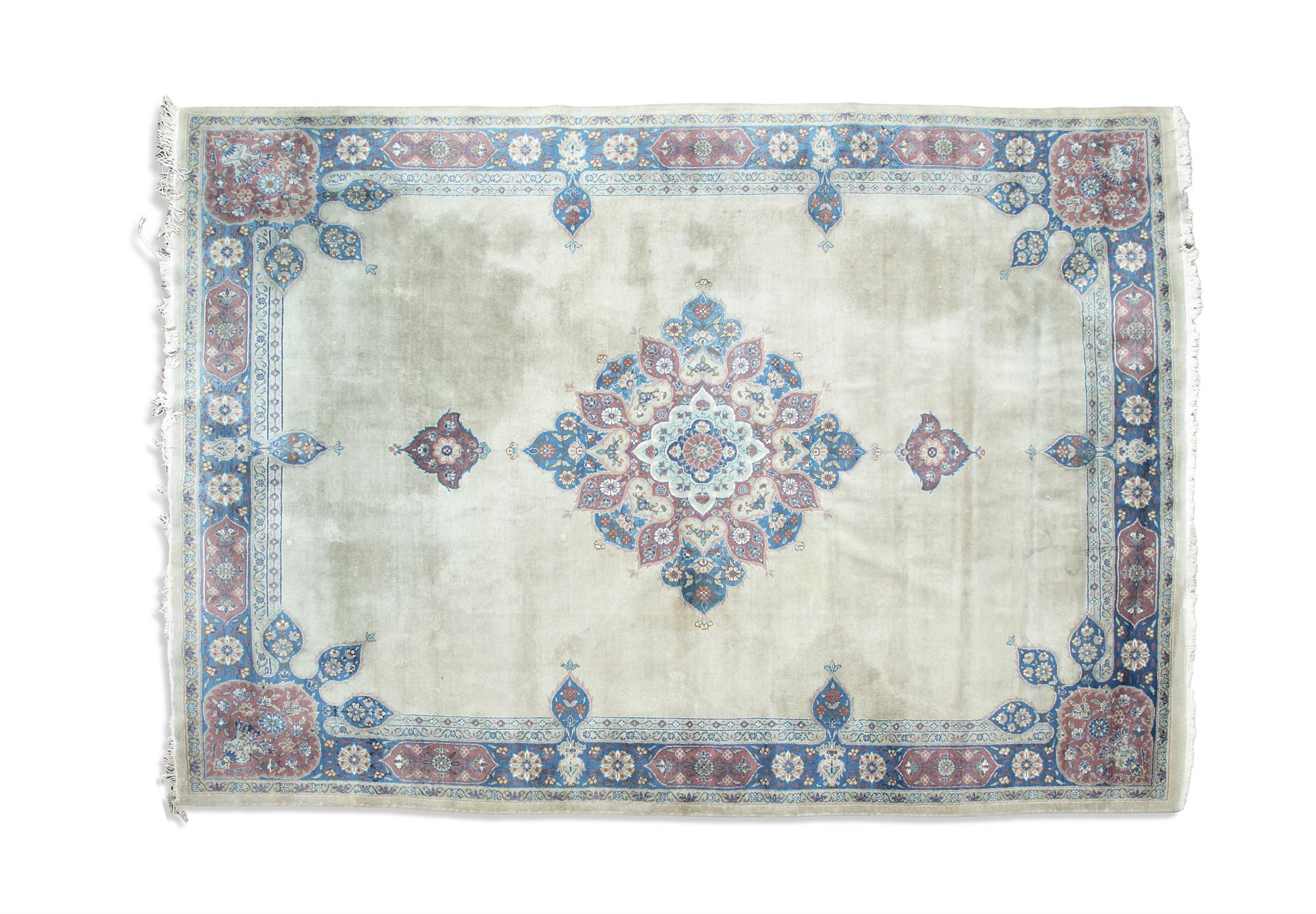 AN INDIAN WOOL CARPET, 20th century, the soft cream ground centre field, woven with large floral