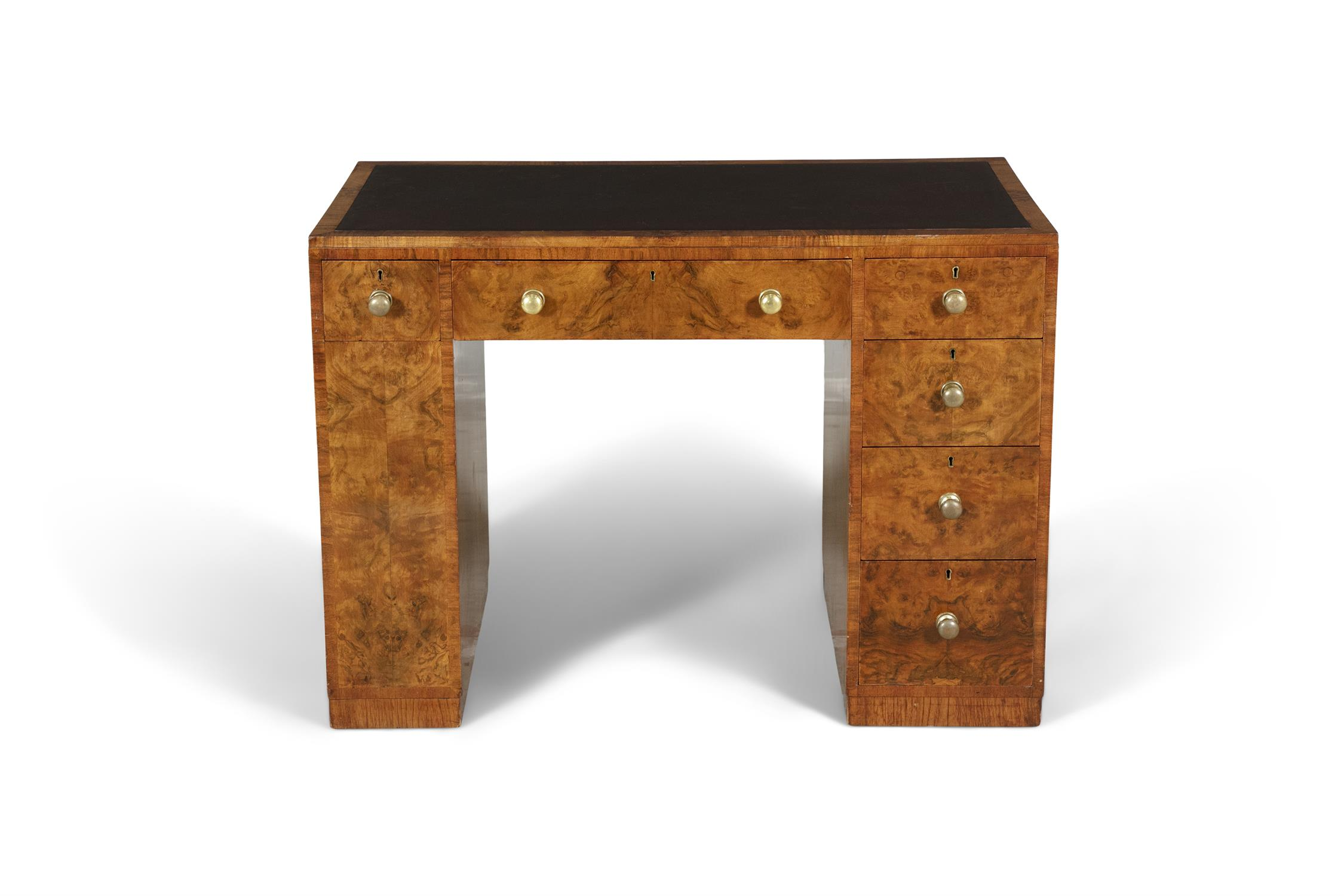 A MID 20TH-CENTURY WALNUT KNEEHOLE WRITING DESK, the rectangular top inset with brown leather