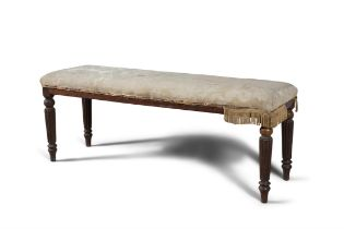 A GEORGE IV MAHOGANY FRAMED WINDOW SEAT, with upholstered seat, on turned fluted legs.