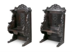 A PAIR OF CONTINENTAL CARVED OAK HALL SEATS, 19th century, in the 17th century style,