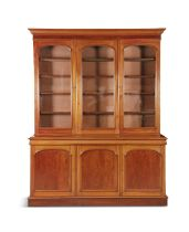 A VICTORIAN MAHOGANY THREE DOOR BOOKCASE, with moulded cornice above plain arched top glazed panel