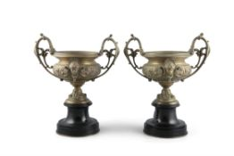 A PAIR OF VICTORIAN BRONZE AND BLACK MARBLE URNS, each with raised scroll side handles and circular
