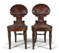 A PAIR OF REGENCY CARVED MAHOGANY HALL CHAIRS, with shell backs and solid seats, raised on turned