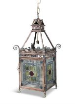 AN EDWARDIAN BRASS AND STAINED GLASS FOUR PANEL HALL LANTERN, of square shape hung on four chains,