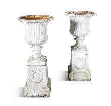 A PAIR OF WHITE PAINTED CAST IRON GARDEN URNS OF CAMPAGNA FORM, with beaded rim and fluted body on