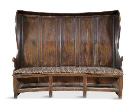 A GEORGE I OAK AND WALNUT TALL BACK SETTLE, the raised five panel back with side guards,