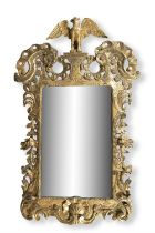 AN IRISH CARVED GILTWOOD MIRROR, C.1740, with scrolled pierced shoulders, filled by an eagle,