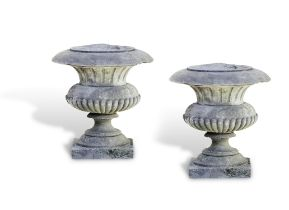 A PAIR OF IRISH 19TH CENTURY CARVED LIMESTONE PIER URNS of baluster form with flared rims and