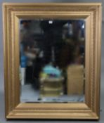 """A large gilt frame rectangular wall mirror with raised foliate border & inset bevelled plate, 40"""""""