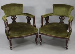 A pair of late Victorian beech-frame tub-shaped chairs with padded seats, backs & arms upholstered