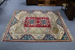 A Turkish small carpet of crimson, blue & ivory ground, with repeating geometric design to centre