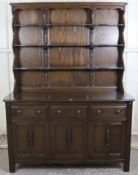 An Ercol dark elm dresser, the upper part fitted open shelves & with panelled back, the base