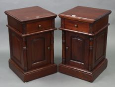 A pair of mahogany-finish bedside cabinets, each fitted frieze drawer above cupboard enclosed by