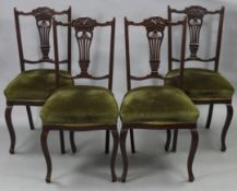 A set of four late Victorian beech splat-back dining chairs with padded seats, & on cabriole legs.