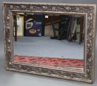 """A large rectangular wall mirror with silvered ornate frame, & inset bevelled plate, 32"""" x 43½""""."""