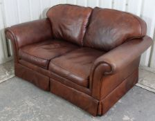 """A tan leather three-piece lounge suite comprising of a two-seater settee, 59"""" long, & a pair of"""