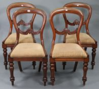 A set of four Victorian mahogany balloon-back dining chairs, with padded drop-in seats & on
