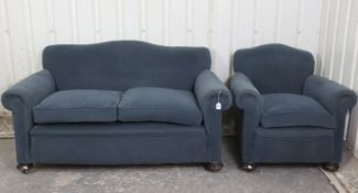 An Edwardian two-seater settee with shaped back, scroll-arms & sprung seat upholstered blue
