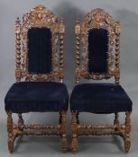 A pair of early 20th century carved oak hall chairs in the Carolean-style.