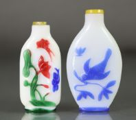 A Chinese overlay glass snuff bottle, with carved decoration to the green, red, pink, & blue overlay