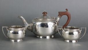 A silver three-piece tea service of plain round form with gadrooned borders, Birmingham 1926 by
