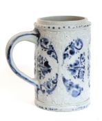 """A German stoneware Westerwald-type cylindrical tankard, with relief decoration; 6½"""" high."""