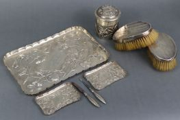 An Edwardian silver dressing table tray with raised crimped border, embossed decoration of