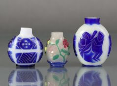 A Chinese overlay glass snuff bottle with carved floral decoration through the blue, green, red,