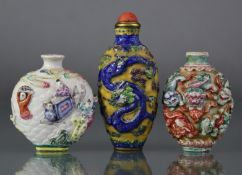 Three Chinese moulded porcelain snuff bottles, the largest decorated with a dragon & phoenix in