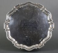 A silver salver with pie-crust edge & three scroll pad feet, inscribed to the centre: