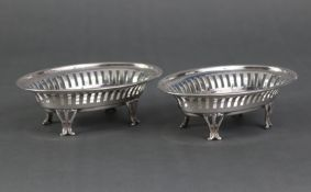 A pair of Edwardian silver oval sweetmeat dishes with pierced sides, each on four shaped feet,