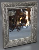 A large rectangular wall mirror in silvered-finish frame with raised geometric border, & inset