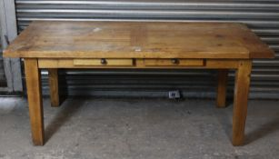 A light oak dining table with rectangular top, fitted two drawers to one side, & on square tapered